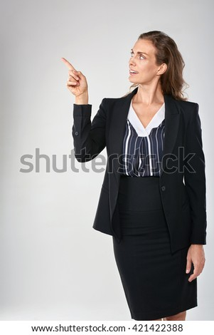 Woman in business suit pointing to the side isolated in studio, for product placement - stock photo