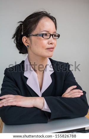 Woman in business suit with closed laptop