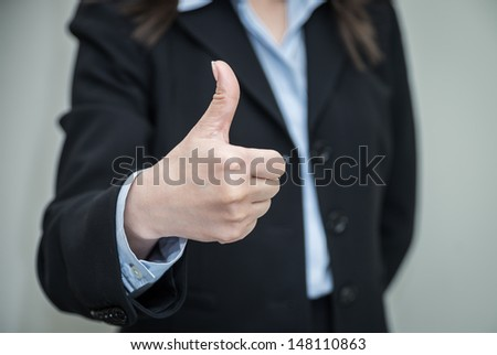Woman in business suit with thumb up with grey background