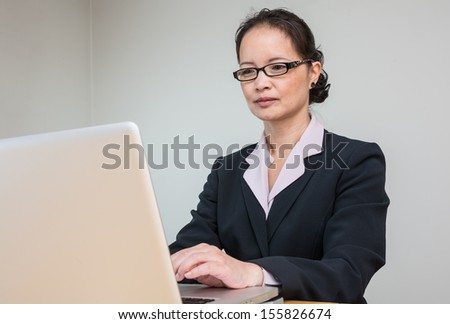Woman in business suit working on laptop
