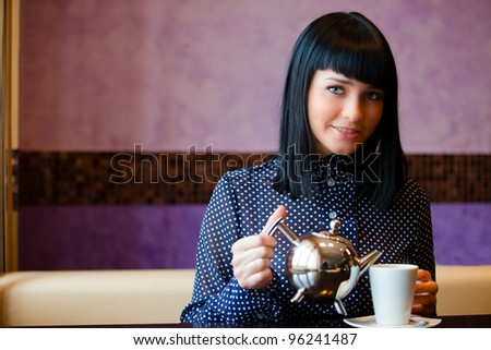 woman in cafe filling cup with teapot