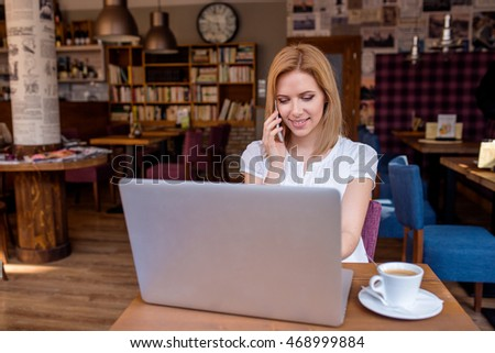 Woman in cafe, talking on phone, working on notebook