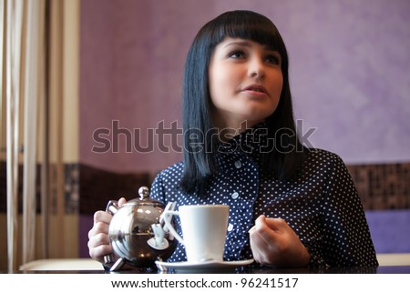 woman in cafe with teapot in hands