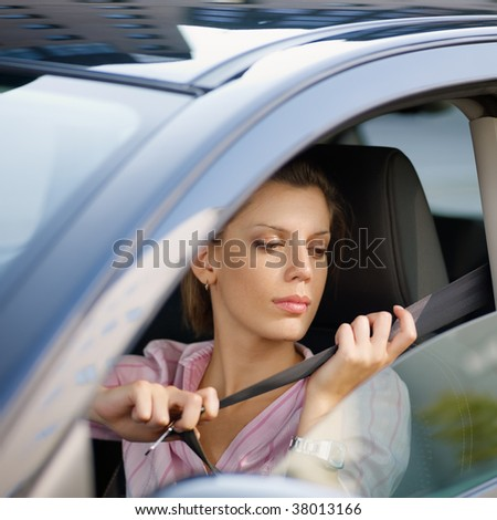 woman in car fastening safety belt