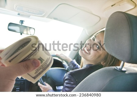 woman in car indoor keeps wheel turning around smiling looking at passengers in back seat idea taxi driver talking to hand hold money dollar who asks for directions right to drive Documents exam - stock photo