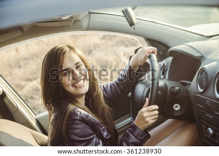 woman in car indoor keeps wheel turning around smiling looking at passengers in back seat idea taxi driver talking to police companion companion who asks for directions right to drive Documents exam - stock photo