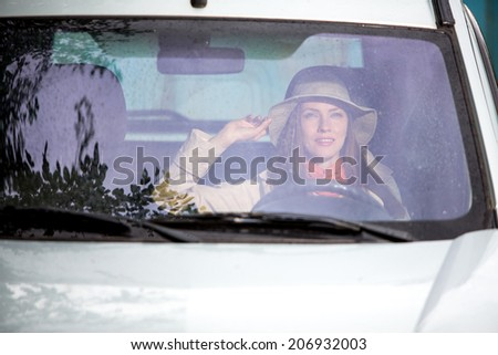 Woman in car indoor keeps wheel turning around smiling looking through window on a rainy day. daylight, focus on face