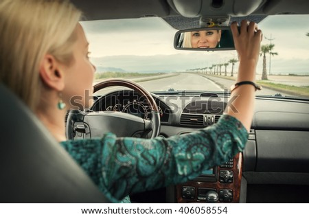 Woman in car look in rear view mirror - stock photo
