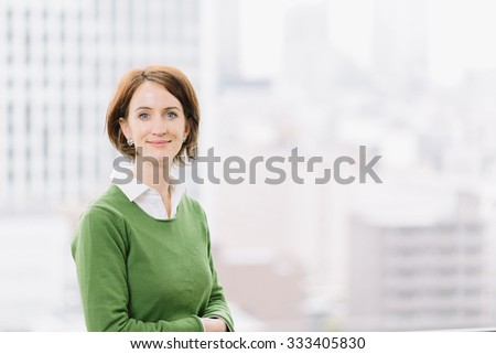 Woman in casual business attire looking at camera confidently by an office window - stock photo