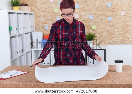 Woman in casual clothes is standing near cork table and looking at blueprints with pencil in hand. Concept of engineer at work