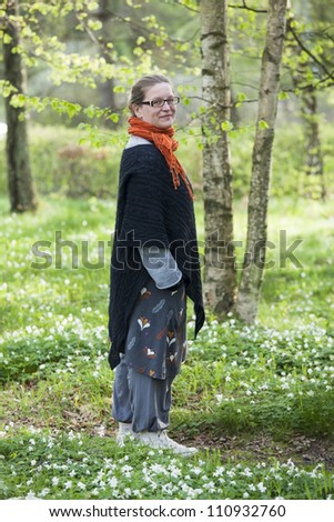 Woman in casual clothes standing on a small path in a forest. White anemones are covering the ground - stock photo
