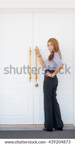 woman in casual life standing in front of the white door and hold Metal handle of