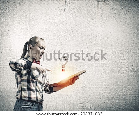 Woman in casual wear holding opened book in hands