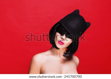 Woman in cat hat. Cap with animal ears. on red background - stock photo
