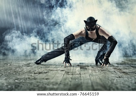 Woman in cat suit with smoke and rain effect. - stock photo