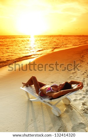 Woman in chaise-lounge relaxing on sunset beach - stock photo