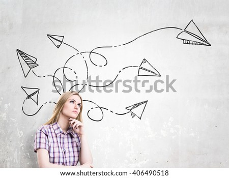 Woman in checked shirt with hand at chin, paper planes drawn over her head, dreaming. Concrete background. Concept of new idea. - stock photo