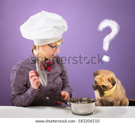 Woman in chef's hat and her dog looking at a pot with a quizzical expression, purple background - stock photo