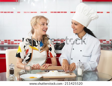 Woman in chef uniform explaining to her younger friend how to make dough - stock photo