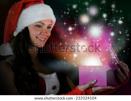 Woman  in christmas hat smiles and holding a gift in magic packing  on a dark background