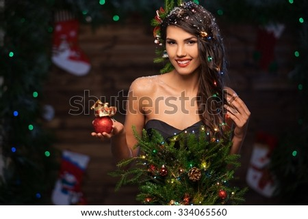 Woman in christmas tree dress in wooden interior holding christmas toy - stock photo