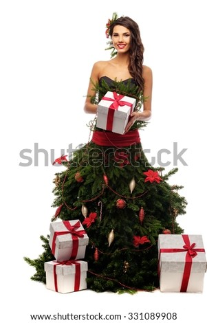 Woman in christmas tree dress with gift box isolated on white - stock photo