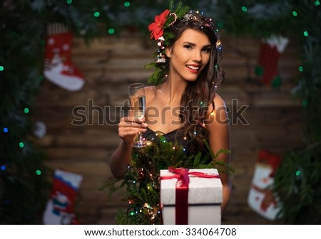 Woman in christmas tree dress with glass of champagne and gift box - stock photo