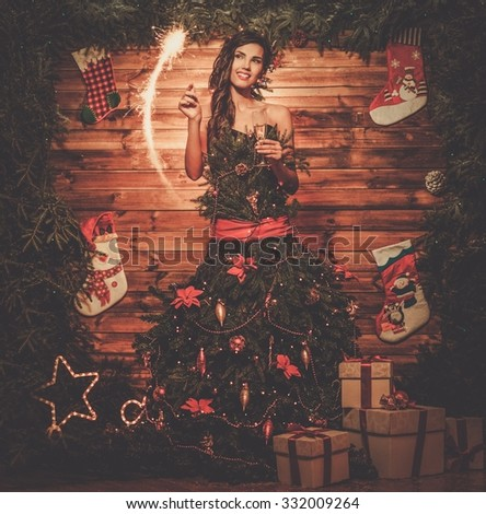 Woman in christmas tree dress with glass of champagne and sparkler  - stock photo