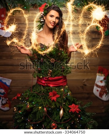 Woman in christmas tree dress writing with sparkler in the air - stock photo