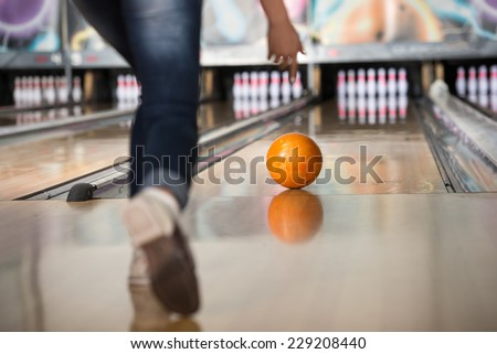 Woman in club for bowling is throwing ball. - stock photo