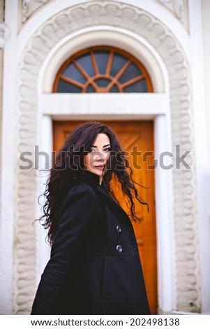 Woman in coat at street near entrance door - stock photo