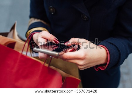 Woman in coat using mobile phone after shopping - stock photo