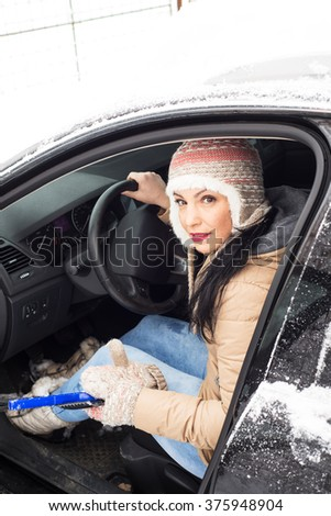 Woman   in  cold day cleaning snow  and trying to go with the car - stock photo