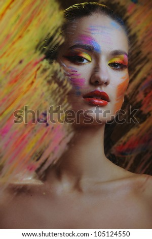 woman in color paint behind the painted glass - stock photo