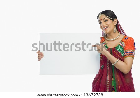 Woman in colorful lehenga choli holding a placard