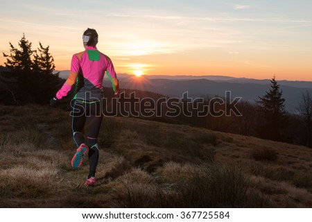 woman in colorful sport dress running in the sunset on the cold fall mountain trail