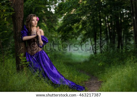 Woman in corset and long purple dress in the fog forest