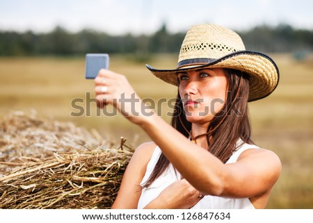 Woman in cowboy hat looking in the mirror. - stock photo