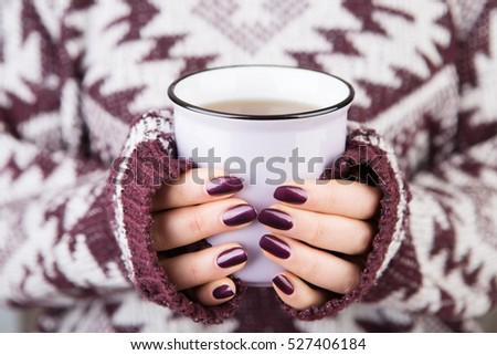 Woman in cozy sweater holding a cup of tea