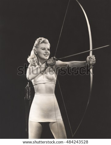 Woman in crop top and mini skirt shooting bow and arrow