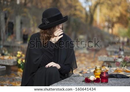Woman in deep sorrow dressed in black at graveyard - stock photo