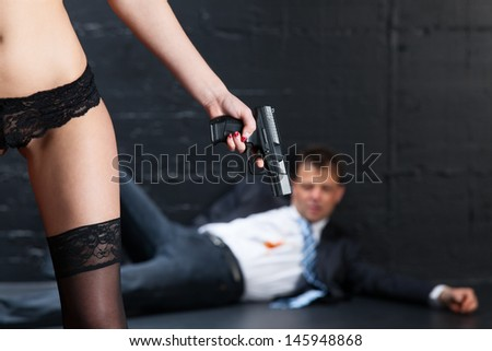 woman in dessous and a gun  - stock photo