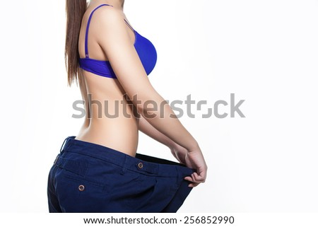 Woman in dieting concept with big pants Big pants weight loss woman - stock photo