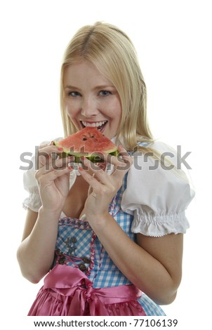 Woman in Dirndl eats Watermelon - stock photo