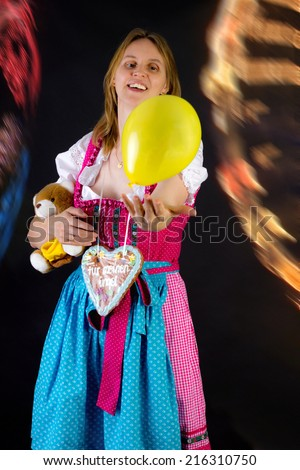 Woman in dirndl enjoying fun fair - stock photo