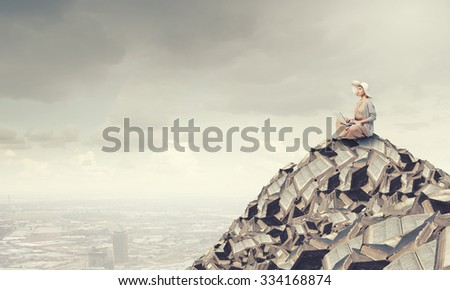 Woman in dress and hat sitting on books and working on laptop - stock photo