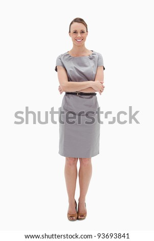 Woman in dress smiling with her arms folded against white background - stock photo