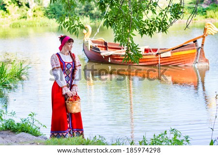 Woman in dress suit stylized Ukrainian folk posing on the river - stock photo