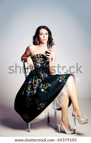woman in elegant dress sit and hold a glass of red wine, studio shot