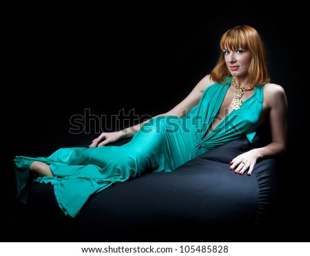 Woman in evening dress reclining on a chair on black background